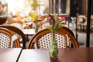 Summer outdoors street cafe. Vase with flower on street cafe table. Restaurant business concept.