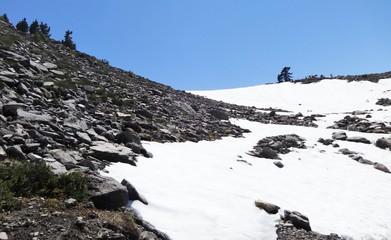 Summer sun heat shrunk a snow field on a hiking trail