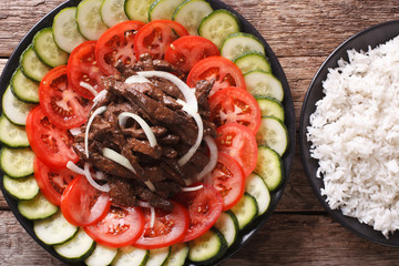marinated roast beef Lok Lak with vegetables and a side dish of rice close-up. Horizontal top view