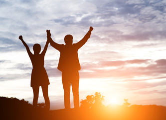 Silhouette of young couple together arms up in the air of happin