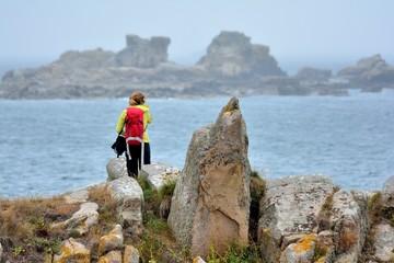 Une jeune randonneuse prend des photos de la côte et la mer à Plougrescant en Bretagne