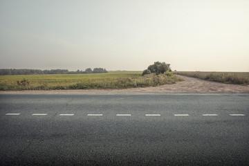 asphalt road through the green field