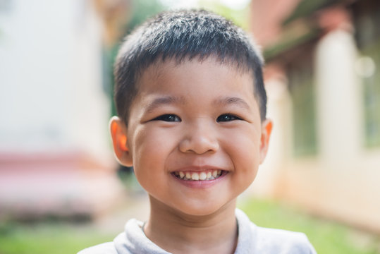 Close up portrait of asian boy smiling in the park.
