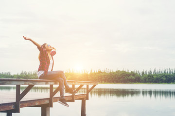 Young hipster woman sitting on pier raised hands,relaxing with n