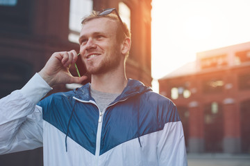 Smiling man speaking on the mobile phone on the street
