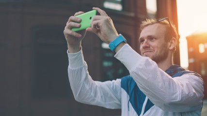 Young cheerful man taking photo with his smartphone on the street