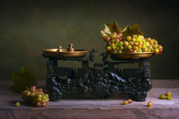 Still life with grapes on old vintage scale.