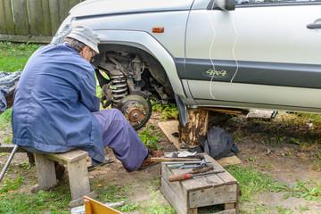 Senior mechanic replaces the vehicle's front wheel.