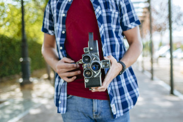 Young man holding an old-fashioned camera
