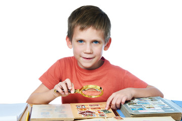 Boy with magnifier looks his stamp collection isolated