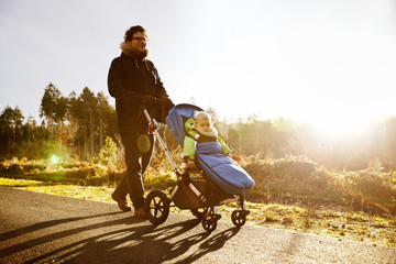 Father and son in buggy on a walk in forest
