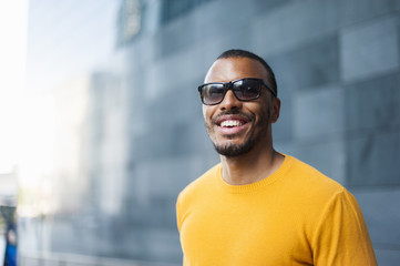 Portrait of smiling man wearing yellow pullover and sunglasses