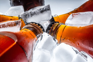 Soda glass bottles in a refrigerated ice cubes on a light background