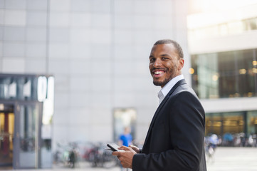 Portrait of smiling businessman with mini tablet