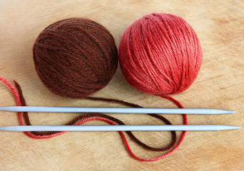 Two skeins of wool and knitting needles on a wooden background.