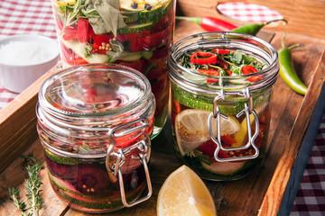 fermentiertes Gemüse in Gläsern auf Holzbrett