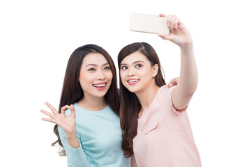 Happy asian woman friends taking a self portrait with a cell pho