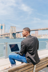 Young Black Businessman Working With the Laptop in Front of the Manhattan Skyline