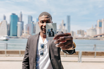 Young Black Man Shows a Pictures of Himself in Front of Manhattan Skyline . Identity Concept