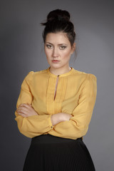 Portrait of beautiful girl in Studio in a yellow blouse and black skirt on a gray background