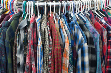 Thrift store flannel shirts on a clothing rack
