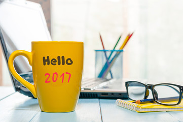Hello 2017 on morning coffee cup. New year concept at business office background