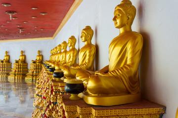 Golden Buddhas sitting in row