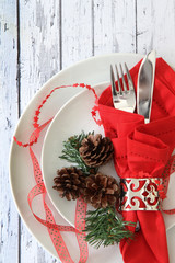Christmas table place setting on white wood background