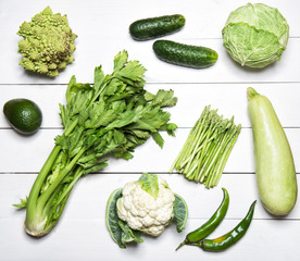 Green vegetables on white wooden table.