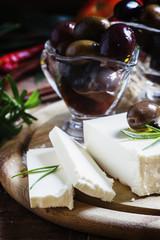 Greek feta cheese, dark wood background, selective focus