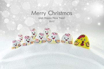 Congratulations on Christmas and New Year 2017. The new 2017 Chinese Year of the rooster. Postcard original idea concept with eggs, rooster family and chickens in the snow.