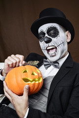 man with mexican calaveras makeup and carved pumpkin