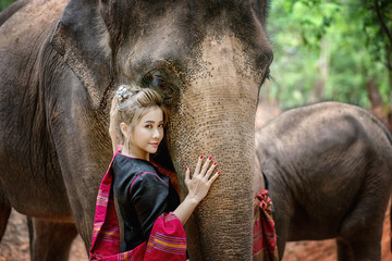 Woman with traditional thai dress hugs her elephant, at elephant