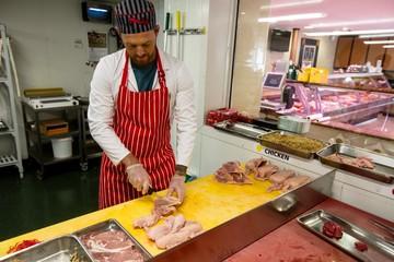 Butcher chopping chicken on work counter