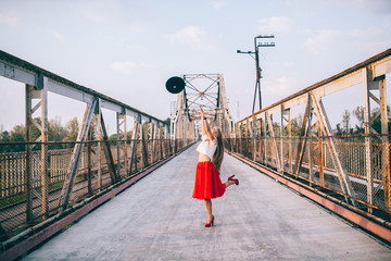 Outdoor lifestyle portrait of happy blonde young woman in stylish casual red dress (skirt) and black hat stay on bridge on the street. Girl throws hat and jump on the brige. Having fun . Long hair