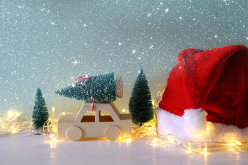 Wooden car carrying a christmas tree next santa claus hat