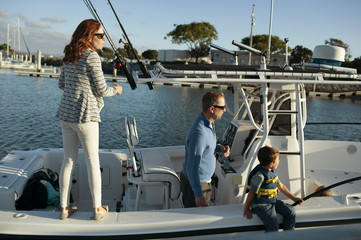 Family traveling in sailboat on sunny day