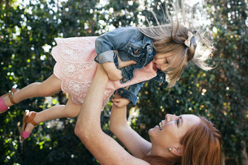 Cheerful mother lifting girl at backyard
