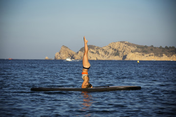 Female athlete exercising on paddleboard at sea against clear sky