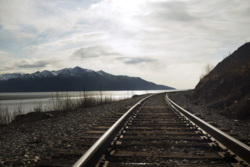 Railroad tracks by sea against sky