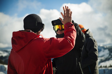 Friends in warm clothing high fiving against sky