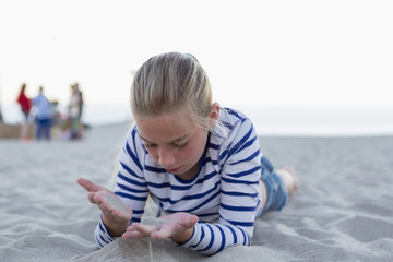 Girl playing with sand while lying at beach