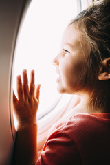 Curious girl looking through airplane window