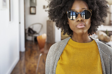 Portrait of woman in sunglasses standing at home