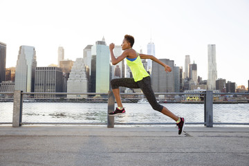 Athlete jumping on promenade by river against clear sky