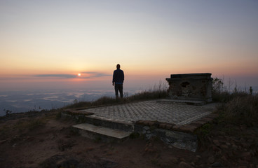 Rear view of man looking at view while standing on mountain during sunset