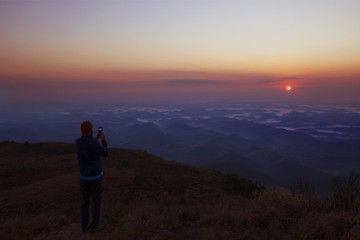 Man photographing scenic view of sunset while standing on mountain