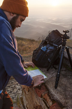 Man looking at map while standing on mountain during sunset