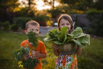 Happy siblings carrying vegetables while standing in backyard