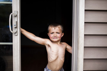 Portrait of shirtless boy standing at doorway